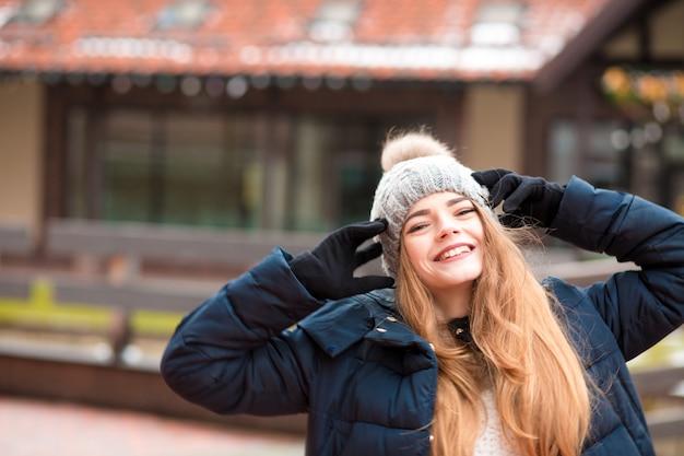 Jovem ruiva positiva, vestindo um casaco de inverno preto e chapéu de malha, posando na rua em kiev