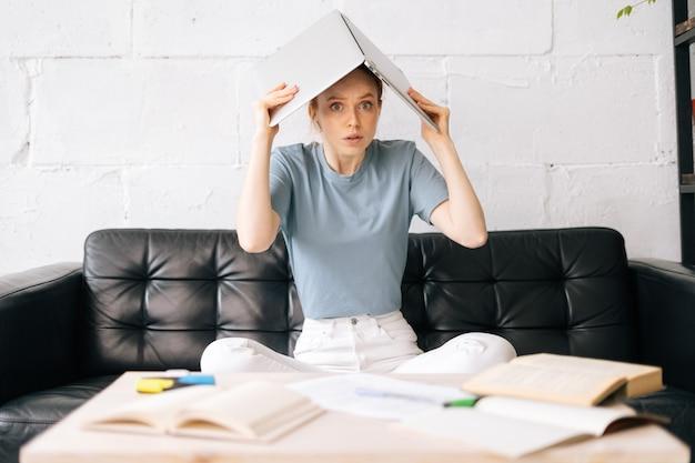 Jovem ruiva preocupada sentada no sofá e colocando o livro na cabeça