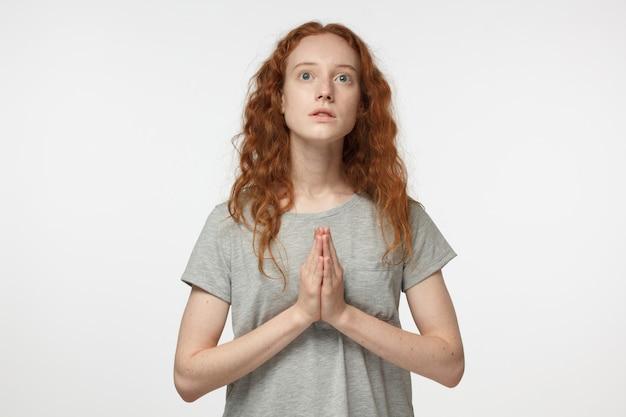 Jovem ruiva religiosa rezando a deus
