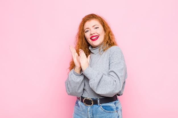 Jovem ruiva se sentindo feliz e bem-sucedida, sorrindo e batendo palmas, dizendo parabéns com aplausos na parede rosa