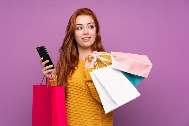 Jovem ruiva segurando sacolas de compras e um telefone celular