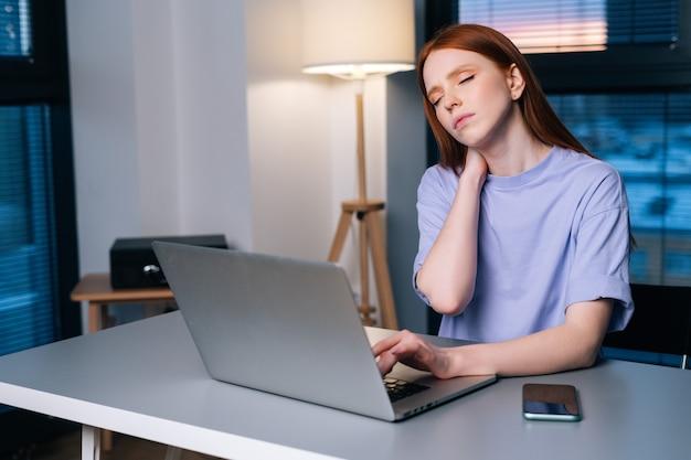 Jovem ruiva sobrecarregada digitando no laptop ativamente sentindo dor no pulso, sentado na mesa perto da janela, à noite. senhora trabalhando no laptop e sofrendo de dores nas mãos, síndrome do túnel do carpo.