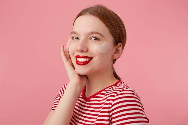 Jovem ruiva sorridente com lábios vermelhos e com manchas sob os olhos, veste uma camiseta listrada vermelha, toca a bochecha, fica em pé e aproveita o tempo livre para cuidar da pele.