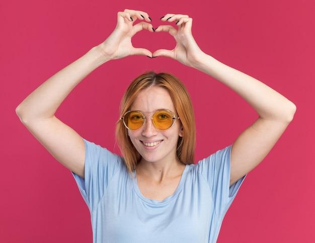Jovem ruiva sorridente com sardas em óculos de sol, gesticulando com o sinal de coração na cabeça, isolada na parede rosa com espaço de cópia