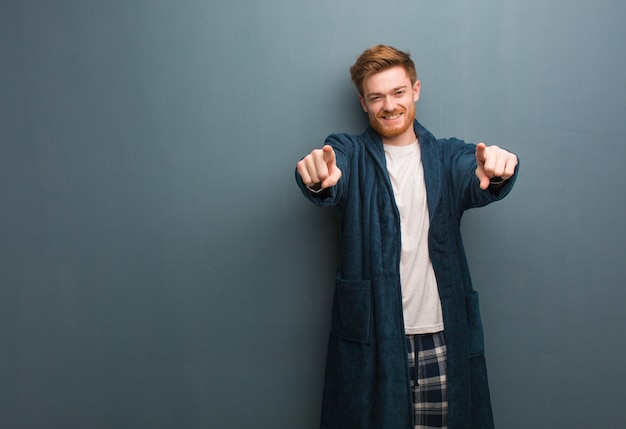 Jovem ruivo de pijama alegre e sorridente apontando para a frente