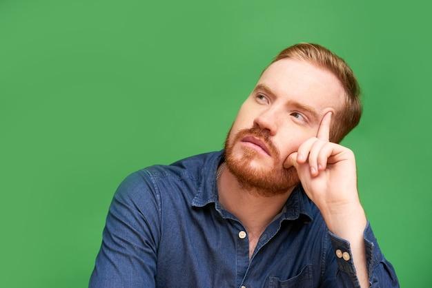 Jovem ruivo sério com barba sentado contra um fundo verde e pensando profundamente
