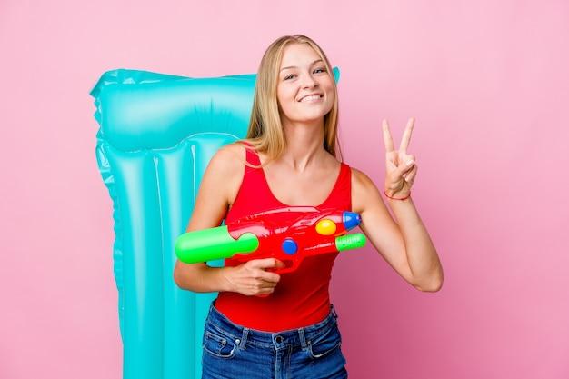 Jovem russa brincando com uma pistola de água com um colchão de ar, mostrando o sinal de vitória e sorrindo amplamente.