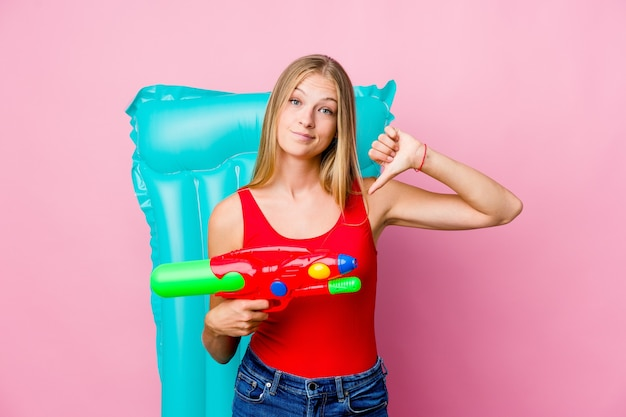 Jovem russa brincando com uma pistola de água com um colchão de ar, mostrando um gesto de antipatia, polegares para baixo. conceito de desacordo