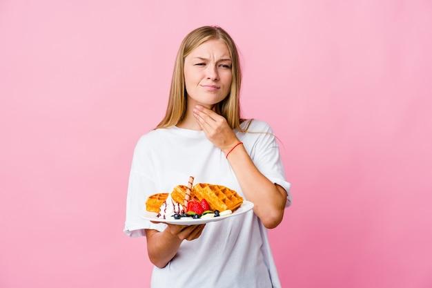Jovem russa comendo um waffle isolado sofre de dor na garganta devido a um vírus ou infecção