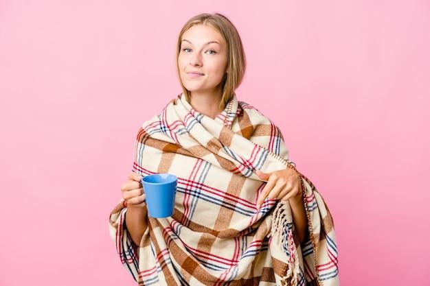 Jovem russa enrolada em um cobertor bebendo café aponta para baixo com os dedos, sentimento positivo
