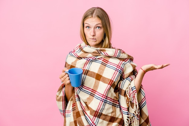 Jovem russa enrolada em um cobertor bebendo café confusa e duvidosa, encolhendo os ombros para segurar um espaço de cópia.