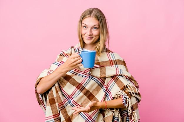 Jovem russa enrolada em um cobertor, bebendo café, segurando algo com as duas mãos, apresentação do produto.