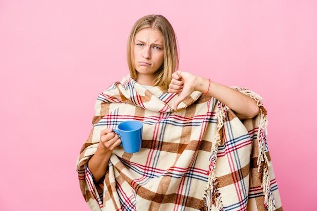 Jovem russa enrolada em um cobertor tomando café, mostrando o polegar para baixo e expressando aversão