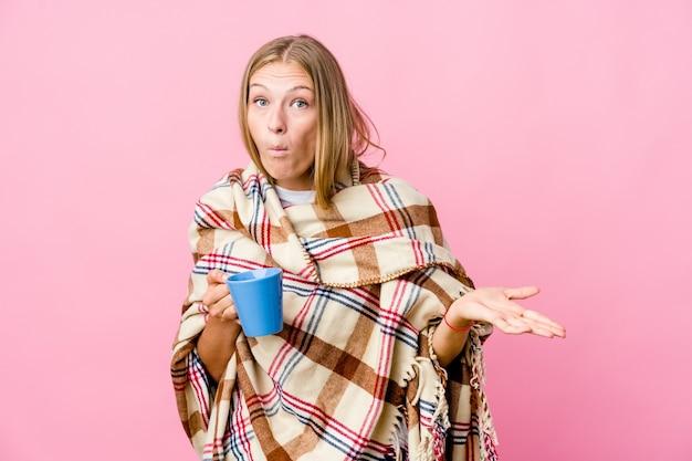 Jovem russa envolta em um cobertor bebendo café encolhe os ombros e abre os olhos confusos.