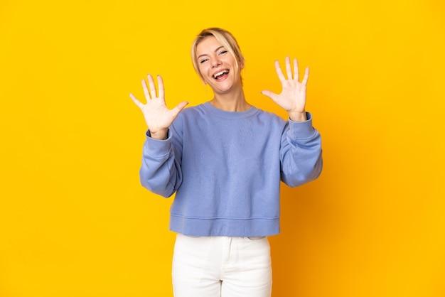 Jovem russa isolada em fundo amarelo contando dez com os dedos