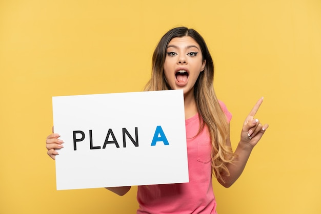 Jovem russa isolada em fundo amarelo segurando um cartaz com a mensagem plano a e pensando