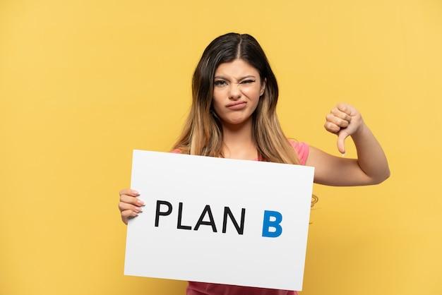 Jovem russa isolada em fundo amarelo segurando um cartaz com a mensagem plano b e sinalizando mal