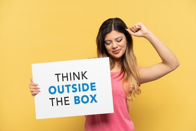 Jovem russa isolada em fundo amarelo segurando um cartaz com o texto pense fora da caixa com gesto orgulhoso Foto Premium