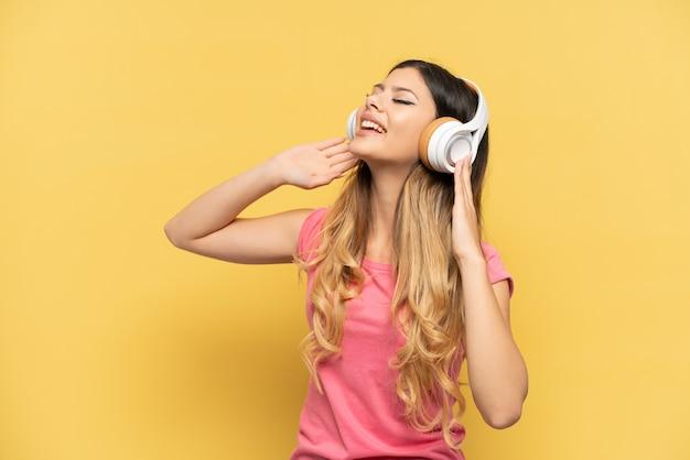 Jovem russa isolada em um fundo amarelo ouvindo música e cantando