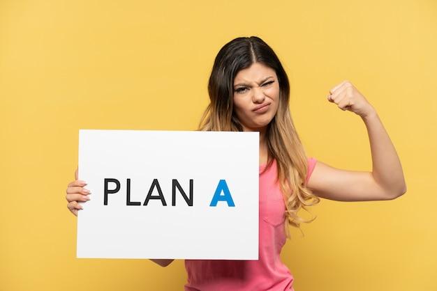 Jovem russa isolada em um fundo amarelo segurando um cartaz com a mensagem plano a fazendo gesto forte Foto Premium