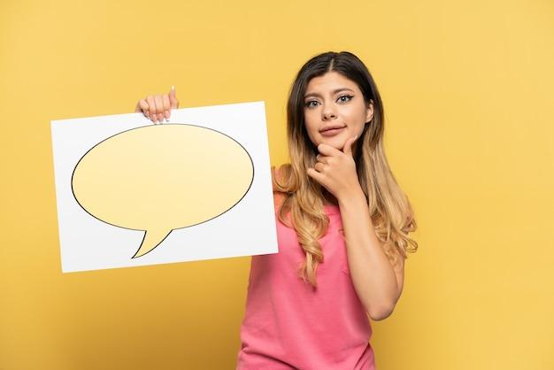 Jovem russa isolada em um fundo amarelo segurando um cartaz com o ícone de balão de fala e pensando