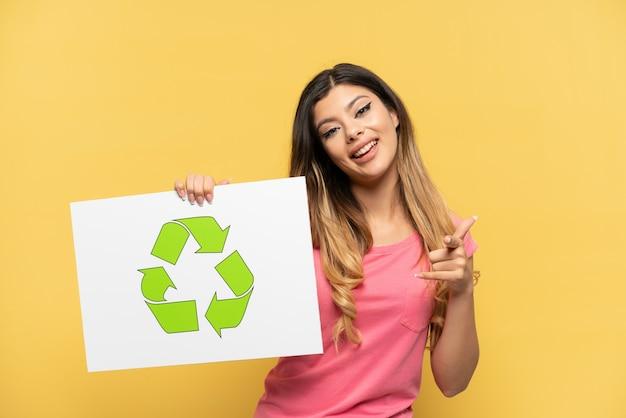 Jovem russa isolada em um fundo amarelo segurando um cartaz com o ícone de reciclagem e apontando para a frente