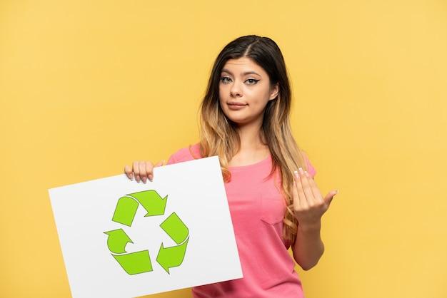 Jovem russa isolada em um fundo amarelo segurando um cartaz com o ícone de reciclagem e fazendo o gesto de vinda