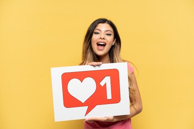 Jovem russa isolada em um fundo amarelo segurando um cartaz com o ícone de semelhante com uma expressão feliz