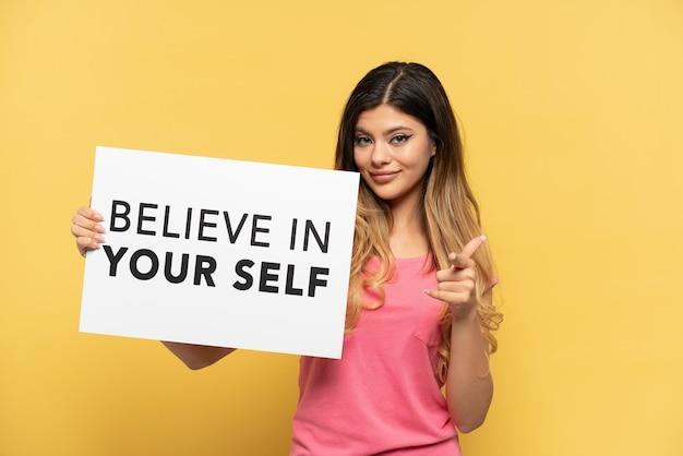 Jovem russa isolada em um fundo amarelo segurando um cartaz com o texto acredite em si mesmo e apontando para a frente