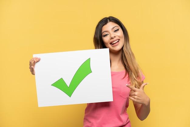 Jovem russa isolada em um fundo amarelo segurando um cartaz com o texto ícone de marca de seleção verde e apontando-o