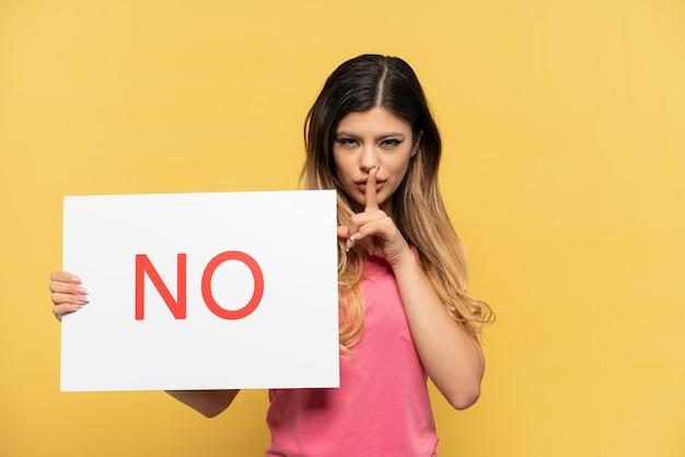 Jovem russa isolada em um fundo amarelo segurando um cartaz com o texto não, fazendo gesto de silêncio