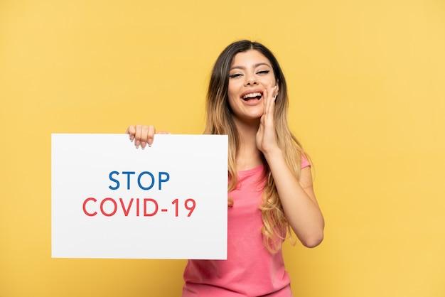 Jovem russa isolada em um fundo amarelo segurando um cartaz com o texto pare covid 19 e gritando