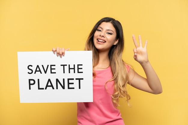 Jovem russa isolada em um fundo amarelo segurando um cartaz com o texto salve o planeta e comemorando uma vitória