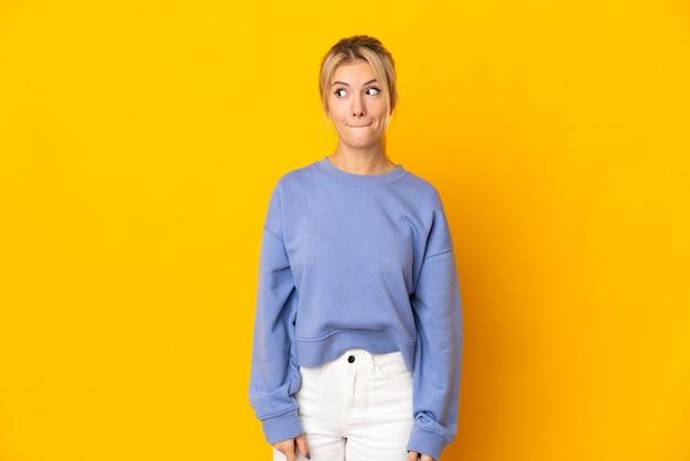Jovem russa isolada em um fundo amarelo tendo dúvidas enquanto olha para cima