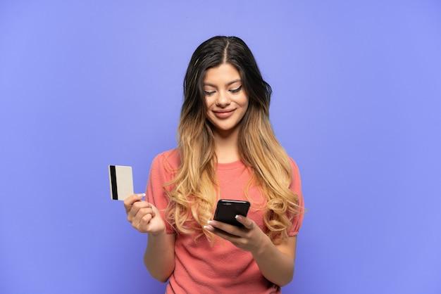 Jovem russa isolada em um fundo azul comprando com o celular com um cartão de crédito