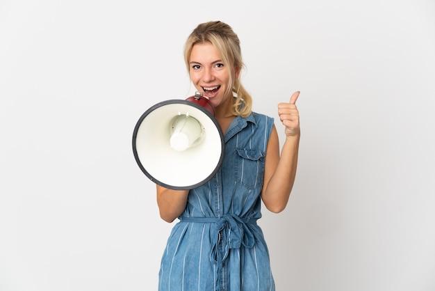 Jovem russa isolada na parede branca gritando em um megafone para anunciar algo e com o polegar para cima