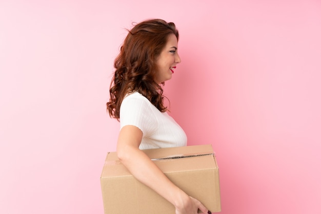 Jovem russa isolado rosa segurando uma caixa para movê-lo para outro site na posição lateral