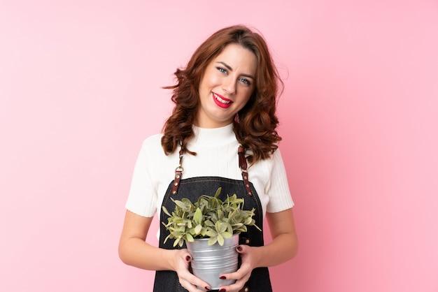 Jovem russa isolado rosa tomando um vaso de flores