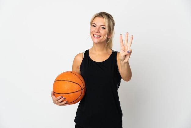 Jovem russa jogando basquete isolado no branco feliz e contando três com os dedos