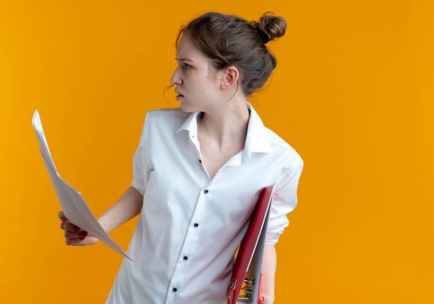 Jovem russa loira séria segurando uma pasta de arquivo e folhas de papel olhando para o lado
