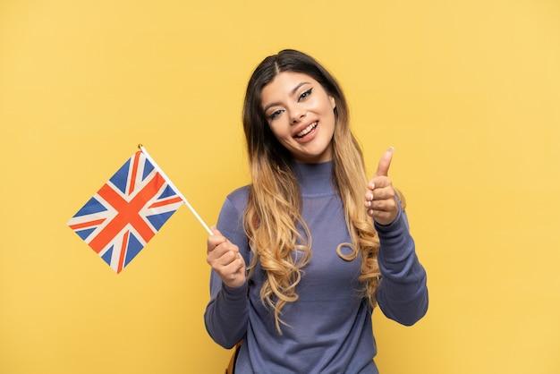 Jovem russa segurando uma bandeira do reino unido isolada em fundo amarelo apertando as mãos para fechar um bom negócio