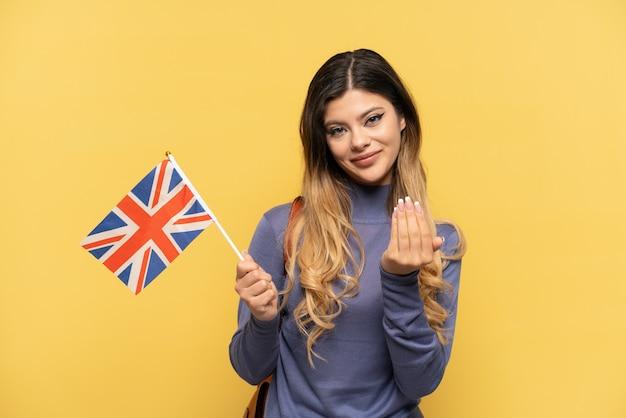 Jovem russa segurando uma bandeira do reino unido isolada em fundo amarelo, convidando para vir com a mão. feliz que você veio