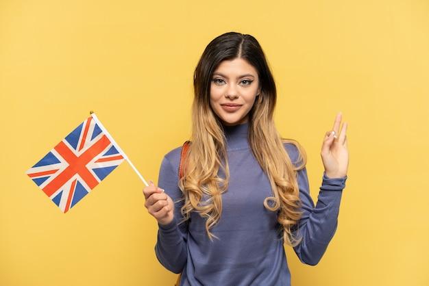 Jovem russa segurando uma bandeira do reino unido isolada em fundo amarelo, mostrando sinal de ok com os dedos