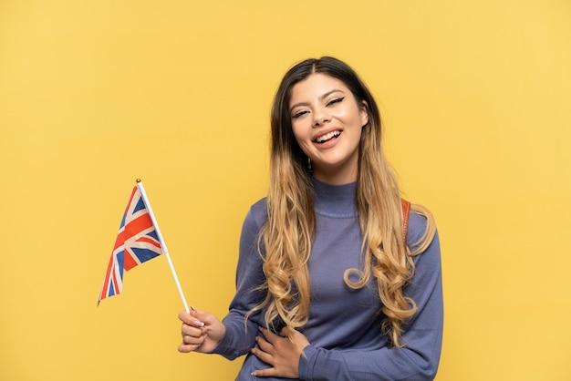 Jovem russa segurando uma bandeira do reino unido isolada em um fundo amarelo e sorrindo muito