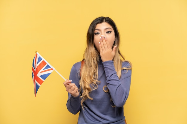 Jovem russa segurando uma bandeira do reino unido, isolada em um fundo amarelo, feliz e sorridente, cobrindo a boca com a mão