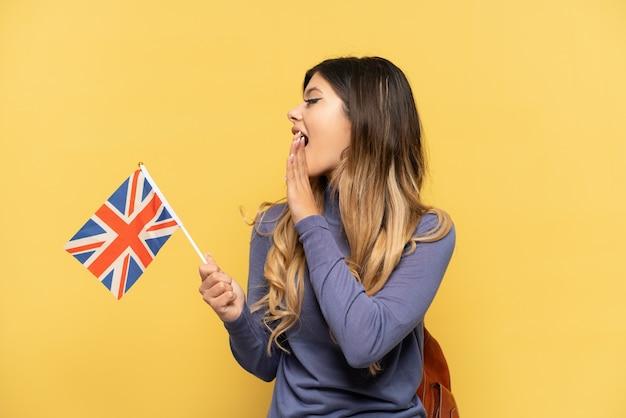 Jovem russa segurando uma bandeira do reino unido isolada em um fundo amarelo, gritando com a boca aberta para o lado