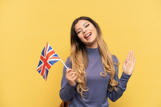 Jovem russa segurando uma bandeira do reino unido, isolada em um fundo amarelo, saudando com a mão com uma expressão feliz