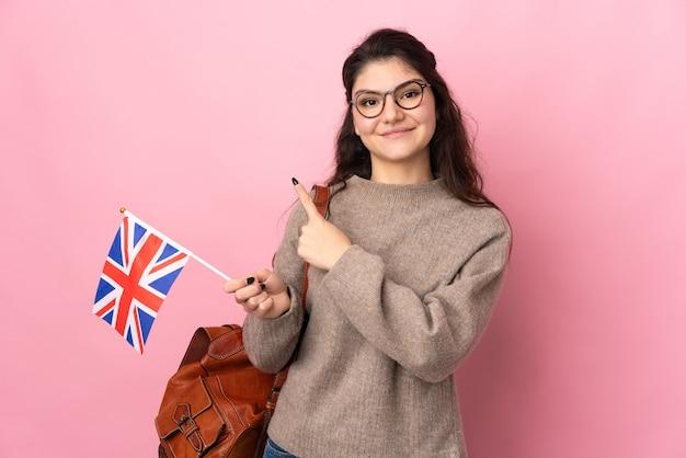 Jovem russa segurando uma bandeira do reino unido isolada em um fundo rosa apontando para o lado para apresentar um produto