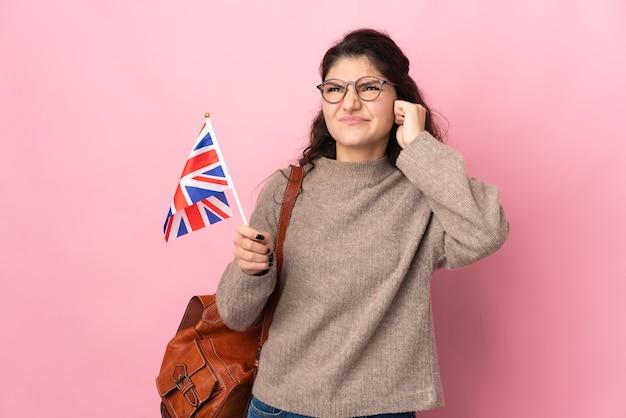 Jovem russa segurando uma bandeira do reino unido isolada em um fundo rosa frustrada e cobrindo as orelhas