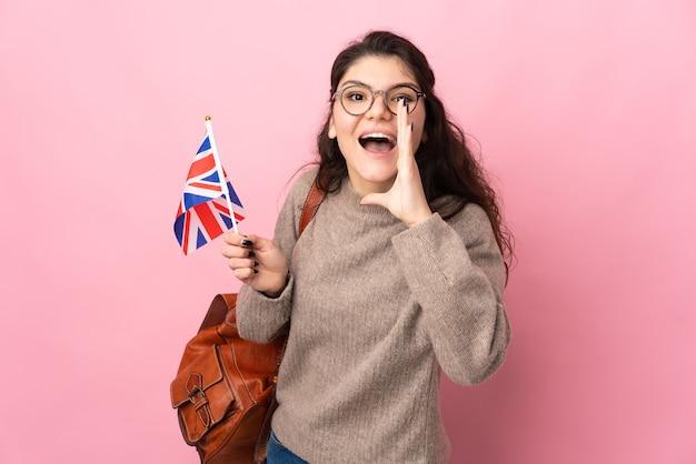 Jovem russa segurando uma bandeira do reino unido isolada em um fundo rosa gritando com a boca aberta